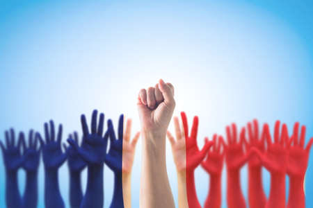 France national flag pattern on leader's fist among people's palm hands  raising up on blue background