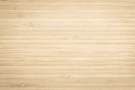 Wood texture old aged bamboo wooden kitchen cutting board grainy detail background in light gold brown beige color
