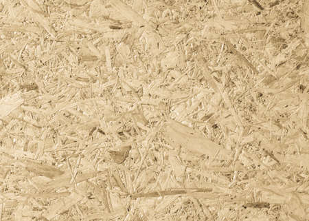 Chipboard, OSB -Oriented strand board particle pressed recycled wood panel background with grainy wooden fiber pattern backdrop in natural yellow cream brown color