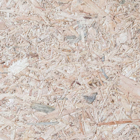 Chipboard, OSB -Oriented strand board particle pressed recycled wood panel background with grainy wooden fiber pattern backdrop in natural beige brown color