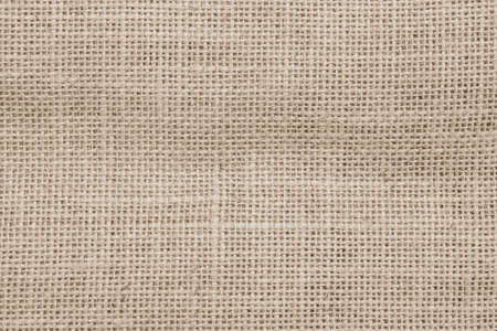 Jute hessian sackcloth woven burlap texture background in sepia cream old aged brown color
