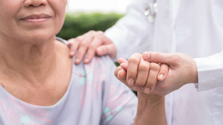 Elderly senior patient (aging old adult person) in nursing hospice home holding geriatrician doctors hand having happy medical health care from hospital carer or caregiver healthcare service