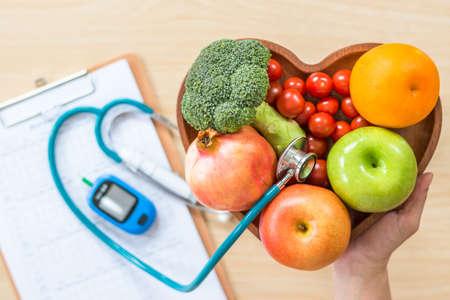 Monitor de diabetes, dieta de colesterol y alimentos saludables que comen el concepto nutricional con frutas limpias en el plato del corazón del nutricionista y el registro de control de azúcar en la sangre del paciente con un kit de herramientas de medición para diabéticos Foto de archivo