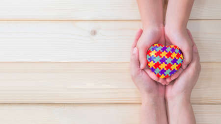 World Autism Awareness day, mental health care concept with puzzle or jigsaw pattern on heart with autistic child's hands supported by nursing woman, family caregiver person or parenting mother