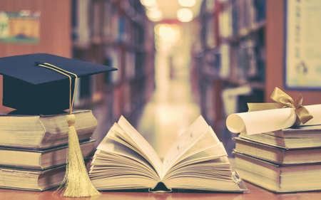 Successo educativo con cappello di laurea, berretto accademico, sparviere e certificato di laurea su libri e libri di testo in classe o nella sala studio della biblioteca Archivio Fotografico