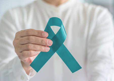 Teal awareness ribbon bow color for Ovarian Cancer, Polycystic Ovary Syndrome (PCOS) and Post Traumatic Stress Disorder (PTSD) Illness support Stock Photo