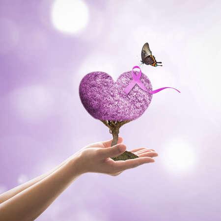 Cinta púrpura lavanda todo tipo de conciencia sobre el cáncer en el árbol del corazón con una mariposa en la mano del voluntario para el concepto de campaña de caridad médica Foto de archivo