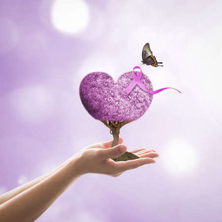 Lavender purple ribbon all kind of cancer awareness on heart tree with butterfly on volunteer's hand for medical charity campaign concept 免版税图像