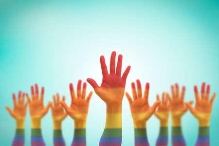 Movimento per la parità di diritti LGBT e concetto di uguaglianza di genere con bandiera arcobaleno sulle mani delle persone in alto