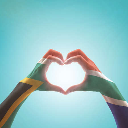 South Africa flag on woman hands in heart shape isolated on mint background for national unity, union, love and reconciliation concept
