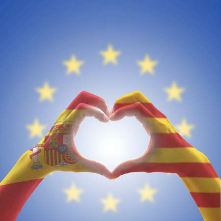 Catalonia Estelada flag  and Spain flag on Catalunya people's heart-shape hands or Catalonia- Spanish unity supporter on EU (European union) flag blue sky background for nationalism concept