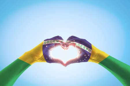 Brazil flag on people hands in heart shape for labor day and national holiday celebration isolated on blue sky background