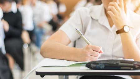 Uczeń przystępuje do egzaminu, intensywnie myśli, pisze odpowiedź w klasie na egzamin wstępny na uniwersytet edukacyjny i koncepcję światowego dnia czytania i pisania Zdjęcie Seryjne