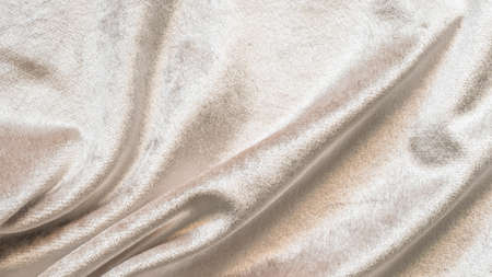 Beige gold velvet background or velour flannel texture made of cotton or wool with soft fluffy velvety satin fabric cloth metallic color material