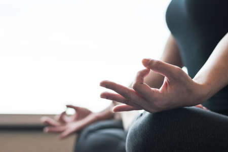 Woman relaxing in yoga lotus pose meditating in silence gym class or home indoor