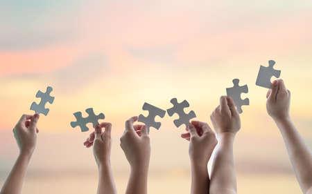 Brainstorming d'idées de travail d'équipe, connexion de partenariat d'équipe pour la résolution de problèmes, recherche de solution dans le concept d'espoir avec des pièces de puzzle dans les mains des écoliers ou des étudiants Banque d'images