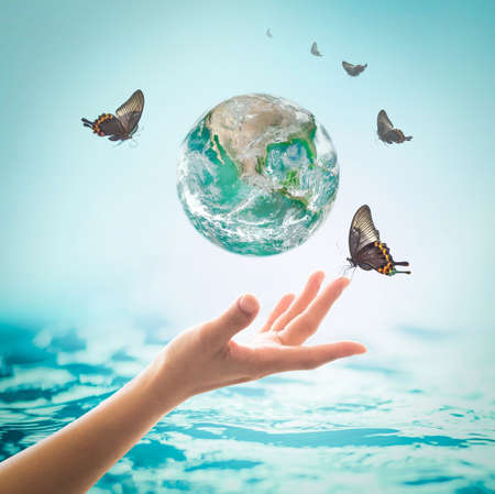 World ocean day,, saving water campaign, sustainable ecological ecosystems concept with green earth on woman's hands on blue sea background