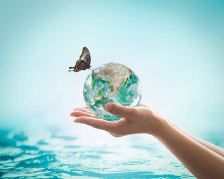 Saving water, world water day, environmental ecology protection, earth day concept with womans hand holding green planet on blur sea or ocean background.
