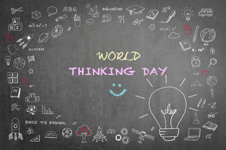 World Thinking Day greeting on teacher's chalkboard with big creative idea lightbulb thought on school or business chalkboard