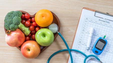 Monitor del diabete, dieta del colesterolo e cibo sano mangiare concetto nutrizionale con frutta pulita nel piatto del cuore del nutrizionista e record di controllo della glicemia del paziente con kit di strumenti di misurazione per diabetici Archivio Fotografico