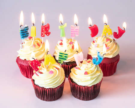 Birthday cake cupcake with cute candle light lit up for childrens birth day anniversary celebration, greeting card and party invitation