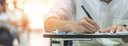 Lo studente dell'esame scolastico sta facendo il test di ammissione educativo in classe, pensando intensamente, scrivendo la risposta nell'aula universitaria, nell'istruzione e nel concetto di giornata mondiale dell'alfabetizzazione
