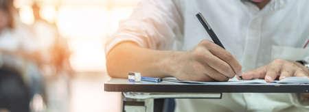 Schulprüfungsstudent, der im Unterricht einen Zulassungstest für Bildungszwecke ablegt, hart nachdenkt, Antworten im Universitätsklassenzimmer, in der Bildung und im Konzept des Weltalphabetisierungstags schreibt
