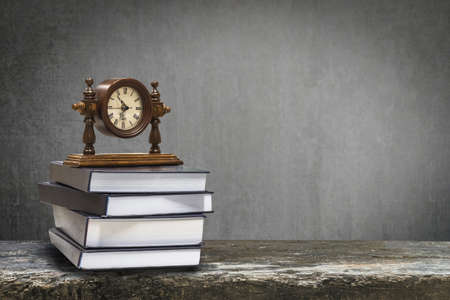 Back to school education concept with clock on book on black chalkboard Banco de Imagens