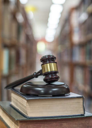Law, legal judgement, litigation and justice concept with judge gavel on law textbook in library archive study room
