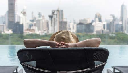 Entspannungsurlaub Reiseurlaub der Geschäftsfrau entspannt sich glücklich auf dem Strandkorb am Pool am Pool im Hotel friedlich mit Park- und Stadtblick und sonnigem Sommerhimmel im Freien Standard-Bild