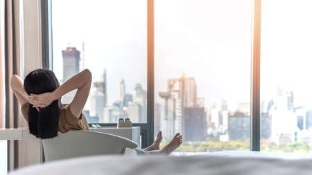 Life quality concept with young woman relaxing and resting in comfort business hotel guest room or luxury home living room looking toward beautiful city view of cityscape Banque d'images