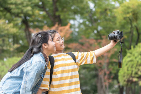 Girls friends, teenager school students with digital camera selfie in the park for vlog, video blog for traveling review