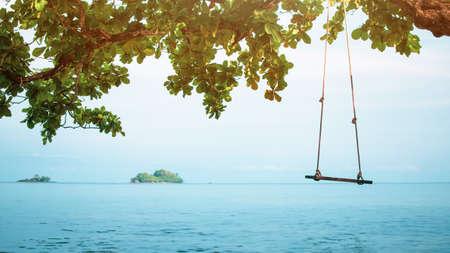 Spiaggia del mare estivo e sfondo dell'isola con oscillazione sull'albero e vista sull'oceano blu paesaggio marino naturale dell'isola per il relax e il concetto di viaggio