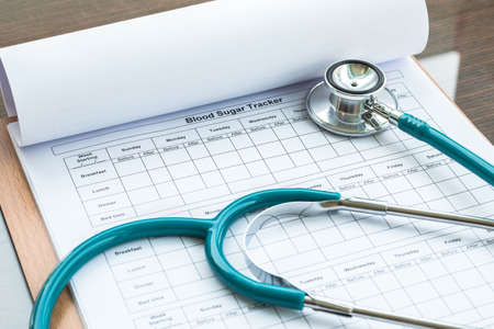 World health diabetes day concept with blood sugar monitoring record and doctor's stethoscope