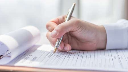 Applicant filling in company application form document applying for job, or registering claim for health insurance Stock Photo