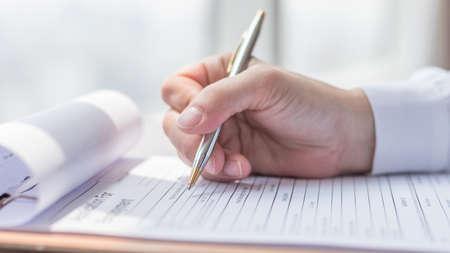 Solicitante que completa el documento del formulario de solicitud de la empresa que solicita trabajo o que registra un reclamo para el seguro de salud Foto de archivo