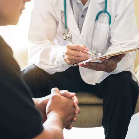 Doctor consulting male patient, working on diagnostic examination on men's health disease or mental illness, and writing on prescription record information document in clinic or hospital office Reklamní fotografie