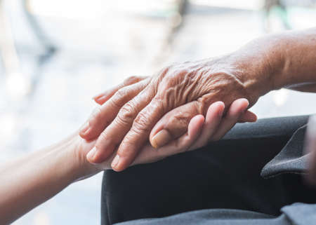 Disability awareness day and aging society concept with Parkinson disease patient or elderly senior person in support of nursing family caregiver's hand