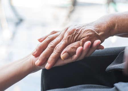 Día de concientización sobre la discapacidad y concepto de sociedad de envejecimiento con paciente con enfermedad de Parkinson o persona mayor anciana en apoyo de la mano del cuidador familiar de enfermería