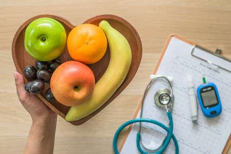 Régime de cholestérol et concept nutritionnel d'aliments sains avec des fruits propres dans un plat cardiaque avec surveillance par un nutritionniste, enregistrement de contrôle de la glycémie avec kit d'outils de mesure Banque d'images