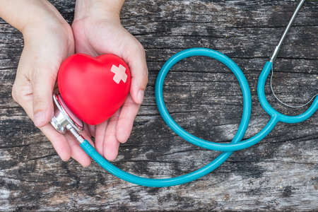 Healthcare medical insurance business and world heart health day concept with red heart on woman's hands support with doctor's stethoscope Stock Photo
