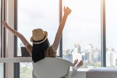 Werk-privébalans, werk- en reislevensstijl ontspanning van jonge freelancer Aziatische werkende vrouw die gezond leven viert en gelukkig rust in comfortabele luxe hotelkamer met gemoedsrust