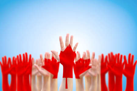 Canada national flag red maple leaf pattern on people hands raising up for citizen rights and election vote concept