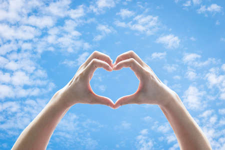 Woman hands in heart shape raising against blue sky with clouds for world kindness day, charity donation, friendship and Valentines love concept 版權商用圖片