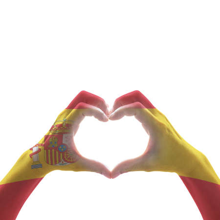 Spain national flag pattern on people's hand in heart shape (isolated with clipping path) on white background