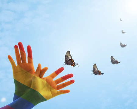 Zero discrimination day concept with rainbow flag pattern on peoples hand in butterfly shape