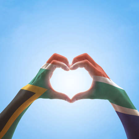 South Africa flag on woman hands in heart shape isolated on blue sky background for national unity, union, love and reconciliation concept