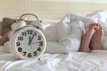 Bedtime sleep with alarm clock at noon or midnight time on bed in bedroom for world lazy day and healthy resting life balance concept Banco de Imagens