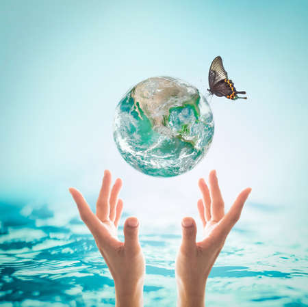 World ocean day, saving water campaign, sustainable ecological ecosystems concept with green earth on womans hands on blue sea background :