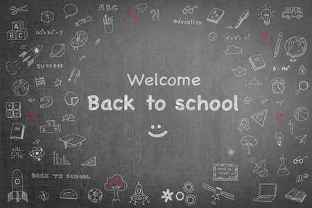 Welcome back to school announcement with doodle on black chalkboard